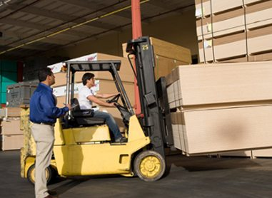 A man watching over a worker operating a forklift, carrying palettes