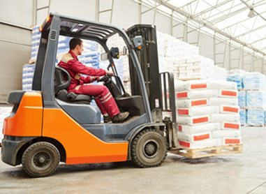 A man operating a forklift, carrying a palette of bags
