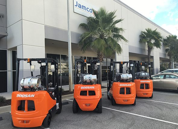 Four Doosan forklifts in a parking lot at the Orlando Jamco location