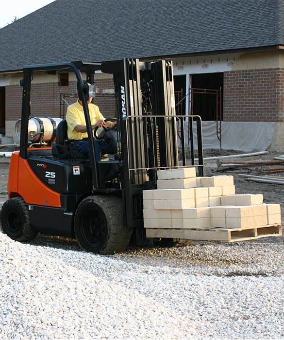 A man operating a forklift carrying concrete pavers