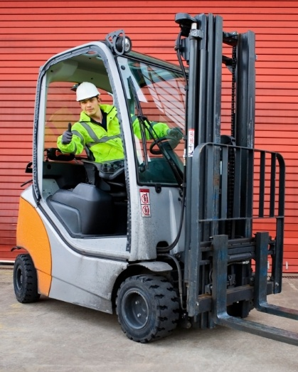 Man operating a forklift, giving a thumbs up