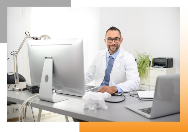 Happy doctor behind a computer