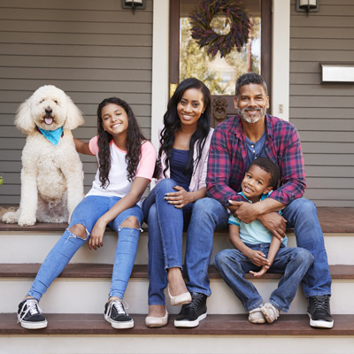 A family and their dog sitting on the front porch