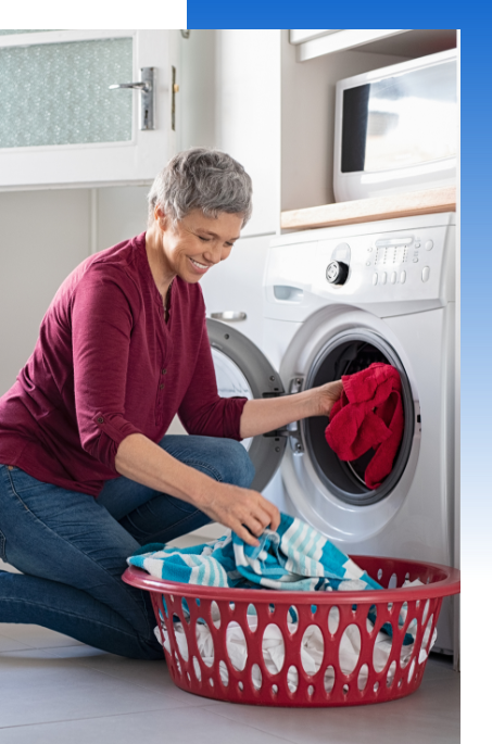 Woman pulling clothes from front loading laundry machine