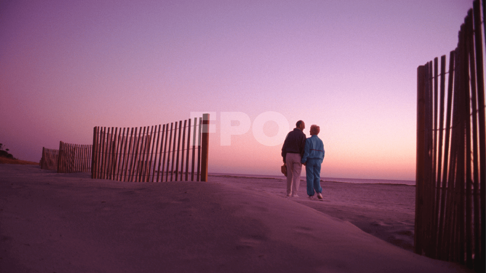 senior couple walking together on the beach at sunset