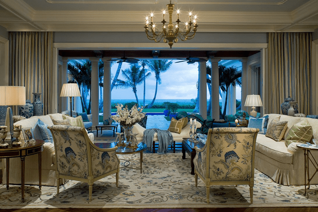 Luxurious living room with white furniture, a brass chandelier, and an ocean view.