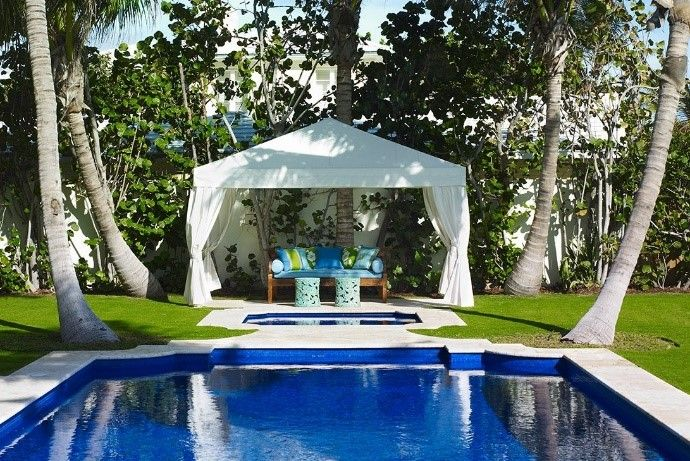 Traditionally designed pool in front of a small cabana with palm trees around it.