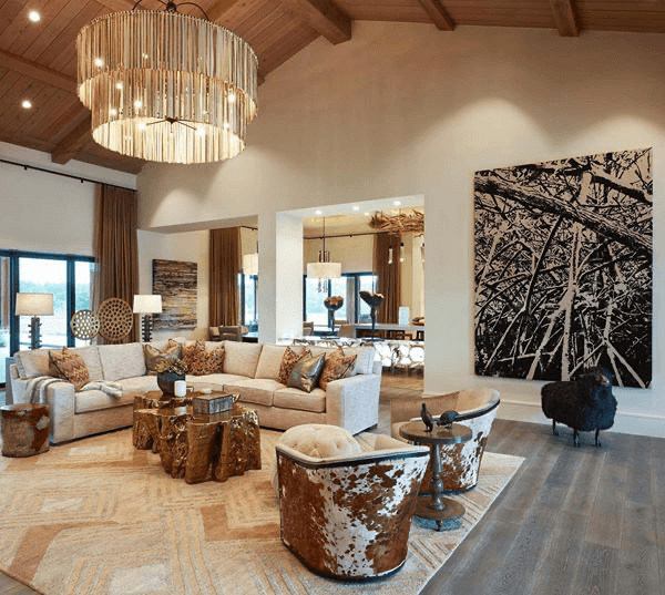 A luxurious ranch with many different textured accessories, such as chairs, paintings, and a chandelier.